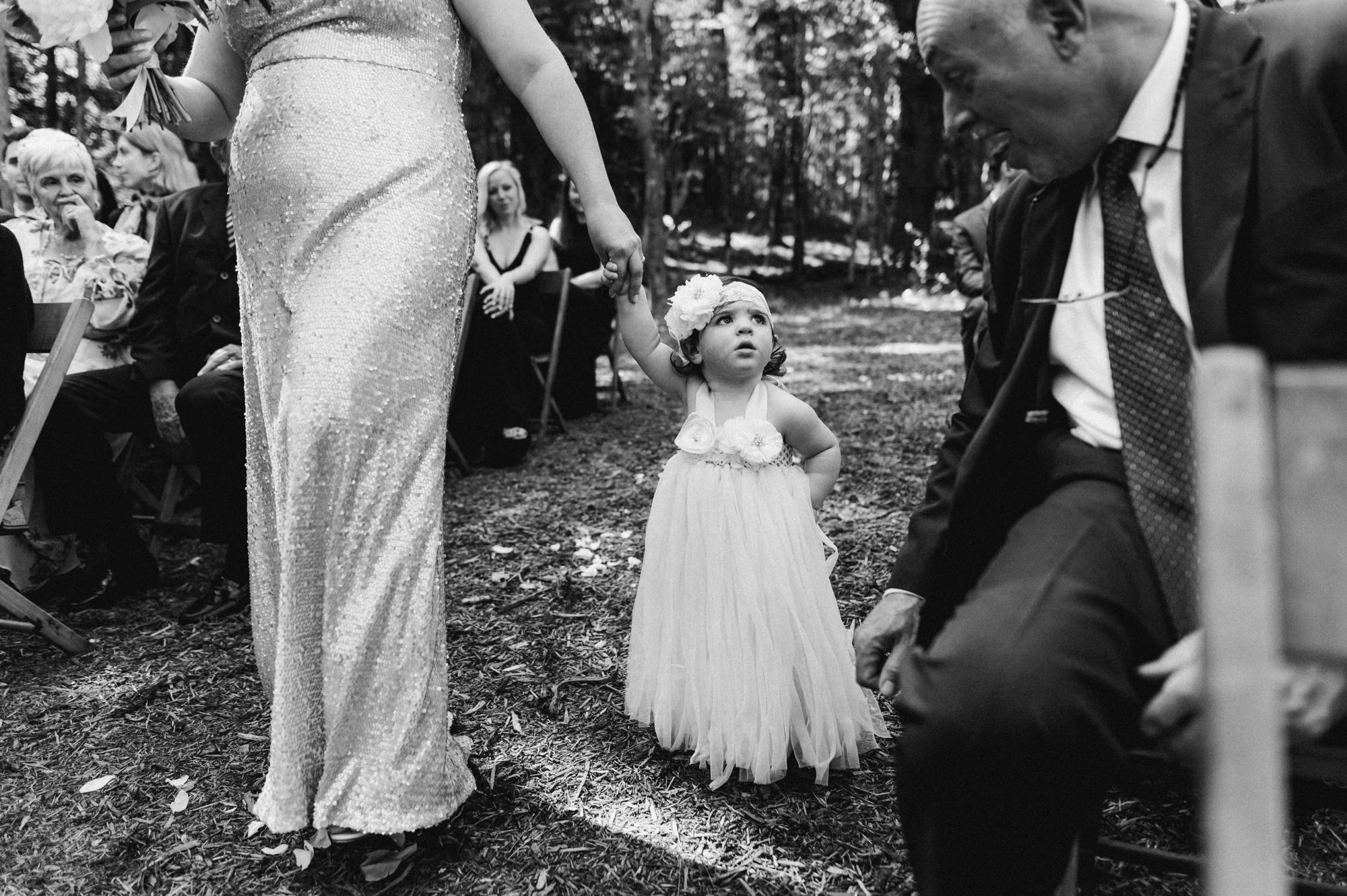 Flower girl walking down the aisle at The Pine Grove wedding ceremony location at Roxbury Barn Estate in the Catskills New York