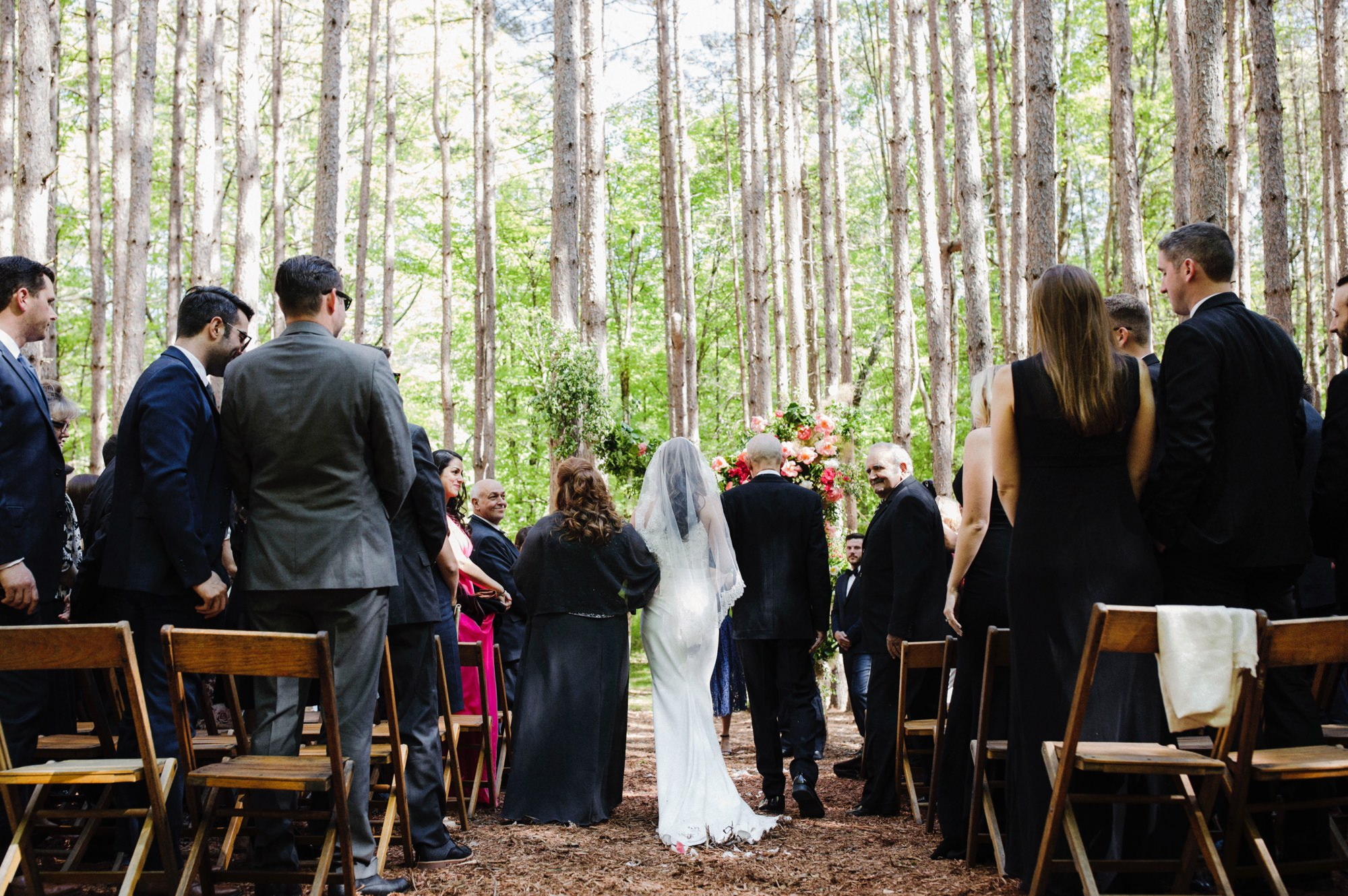 bride walking down the aisle at The Pine Grove wedding ceremony location at Roxbury Barn Estate in the Catskills New York