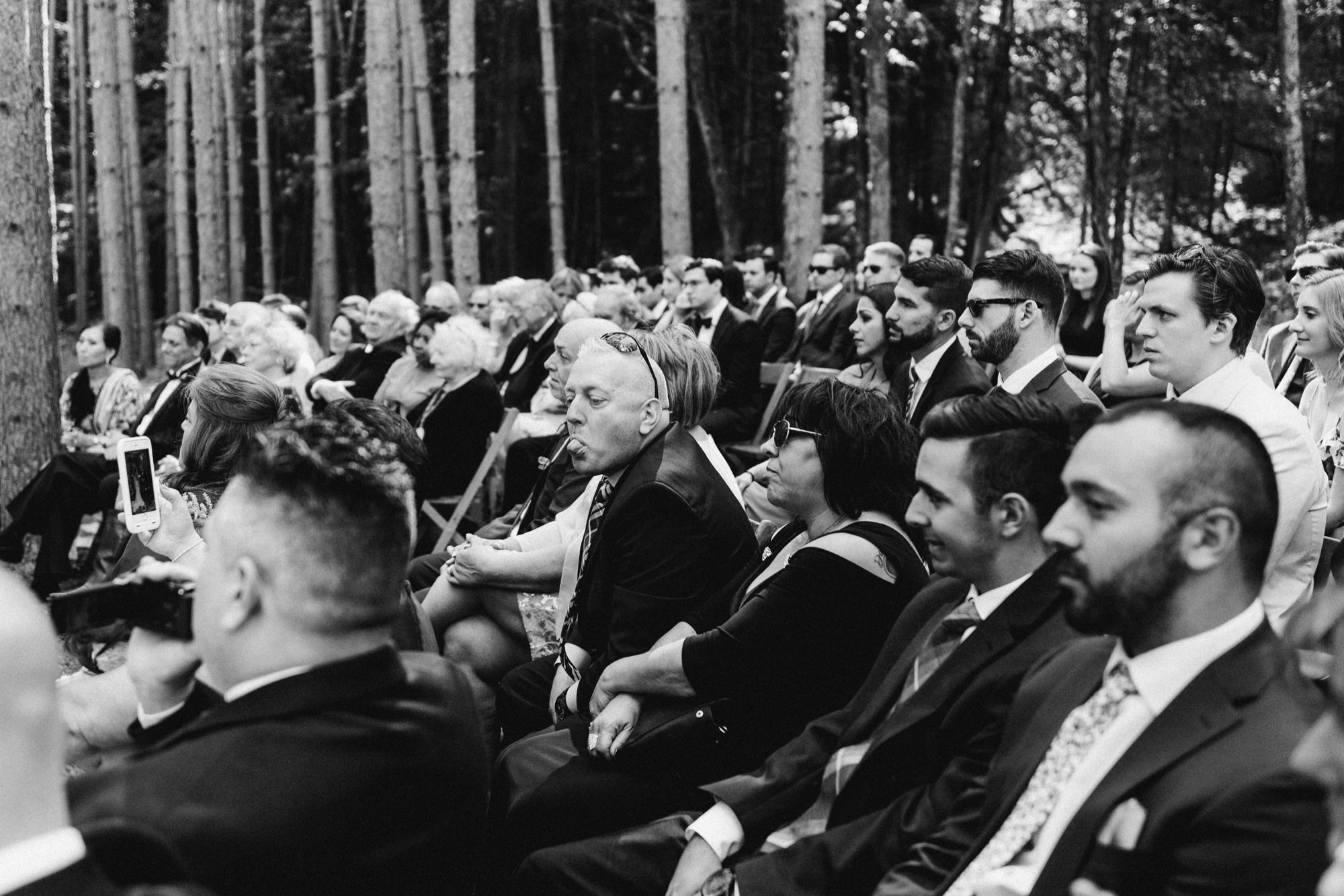 Guest poking out tongue during wedding ceremony at the Pine Grove location at Roxbury Barn Estate in the Catskills New York