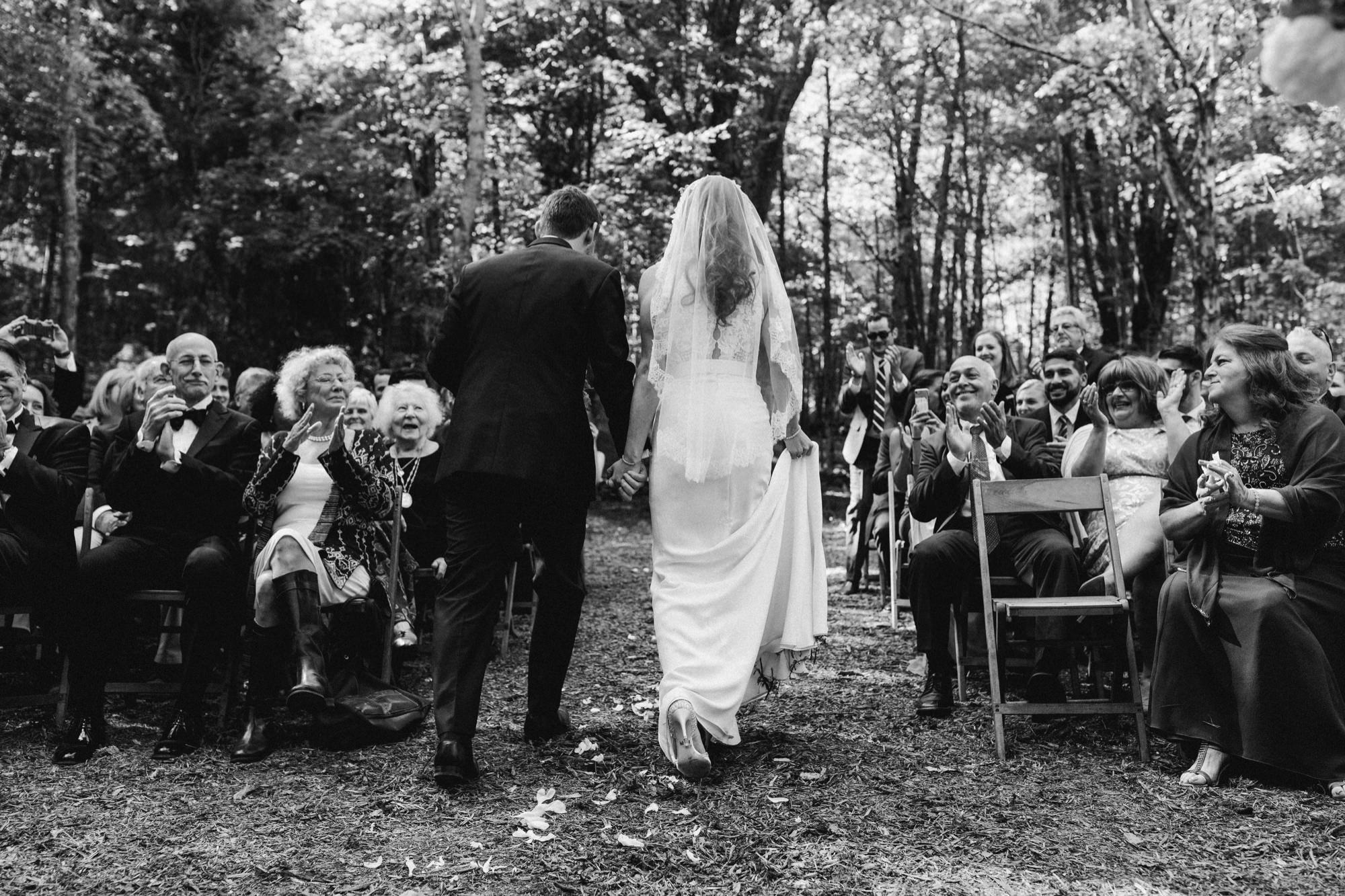 bride and groom departing ceremony at the Pine Grove location at Roxbury Barn Estate in the Catskills New York