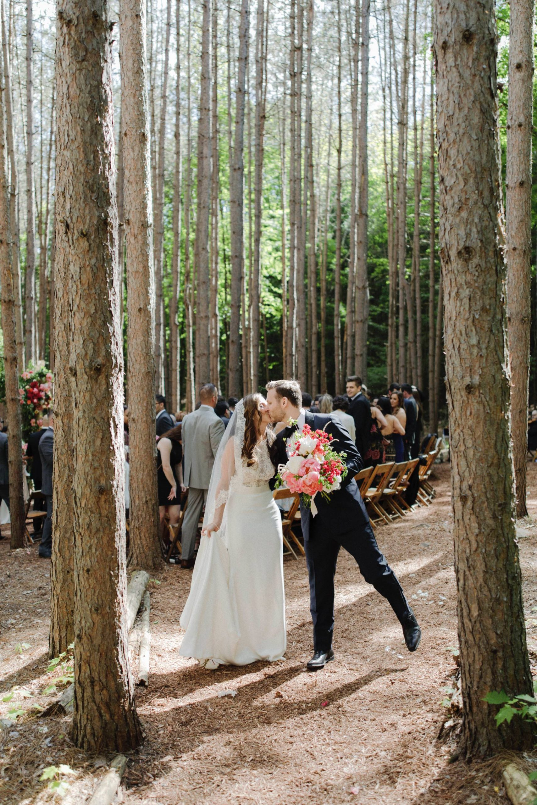 bride and groom exchanging a kiss as walking back down the aisle at the Pine Grove location at Roxbury Barn Estate in the Catskills New York