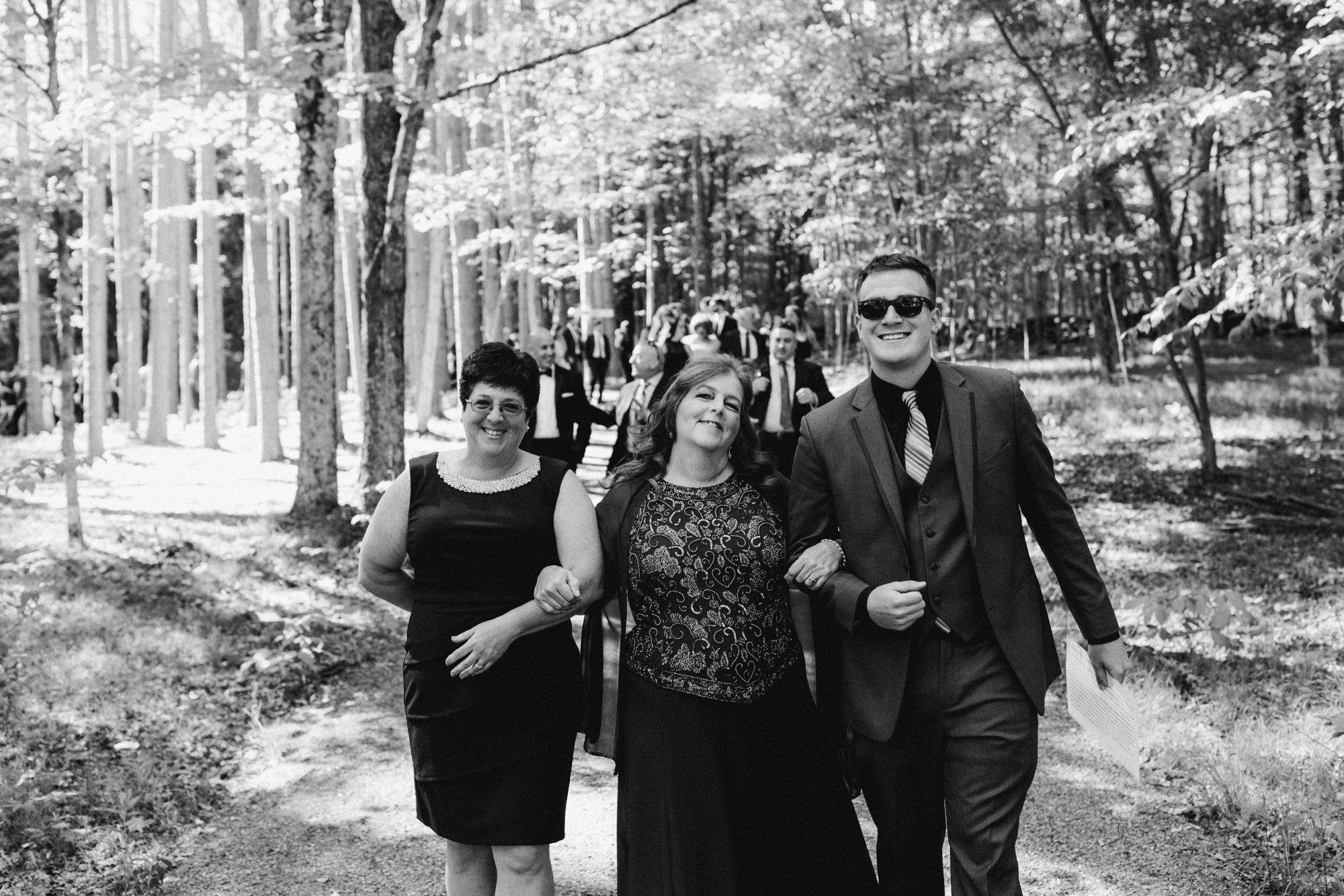 Guests at bride and groom walking back down the aisle at the Pine Grove location at Roxbury Barn Estate in the Catskills New York